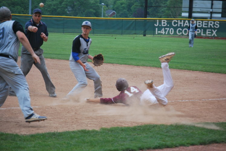 Wheeling Central's Chris Furka (14) slides into first base as Tyler Consolidated's Dylan Roberts takes the throw in Tuesday's Game 1 of the West Virginia Class A Region One Final.