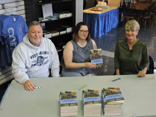 Photo by Alan Olson Author C.J. Plogger, from left, contributor Jordan Gray and corrections officer Maggie Gray welcome visitors during a book signing Thursday at the former West Virginia Penitentiary.