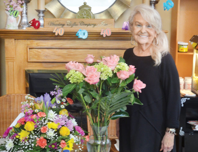 Photo by Scott McCloskey Mary Ann Lokmer, owner of Wheeling Coffee & Spice Co. Inc., is shown with celebratory flowers  Friday on the 40th anniversary of the  business.