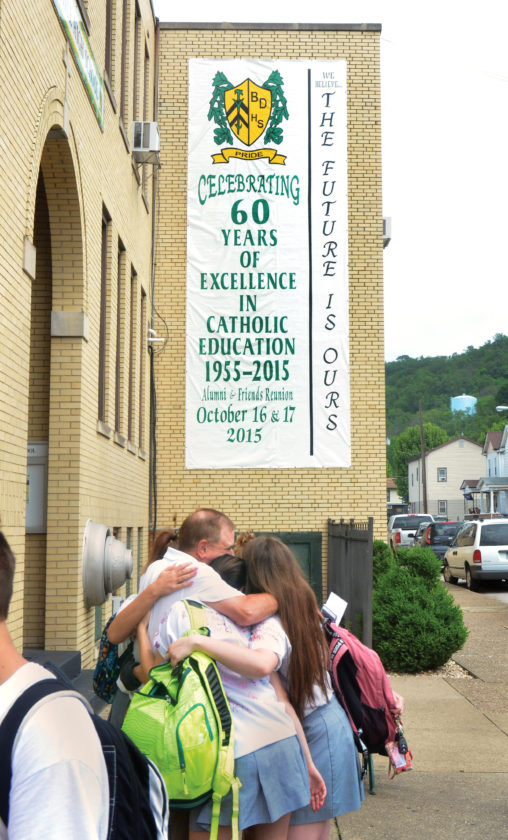 Photo by Scott McCloskey Bishop Donahue High School students who had their final day of classes Friday give one of the teachers a group hug in front of the main entrance. The school is closing after more than 60 years in operation.