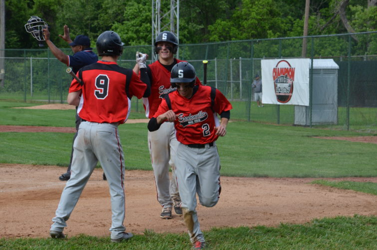 Big Red's Nick Scott (9) congratulates Mitchell Gulan (rear) and Carlo Biasi (2) after they scored on Alec  Taylor's  two-run  single in the third inning Friday.  Photo by  Kim North