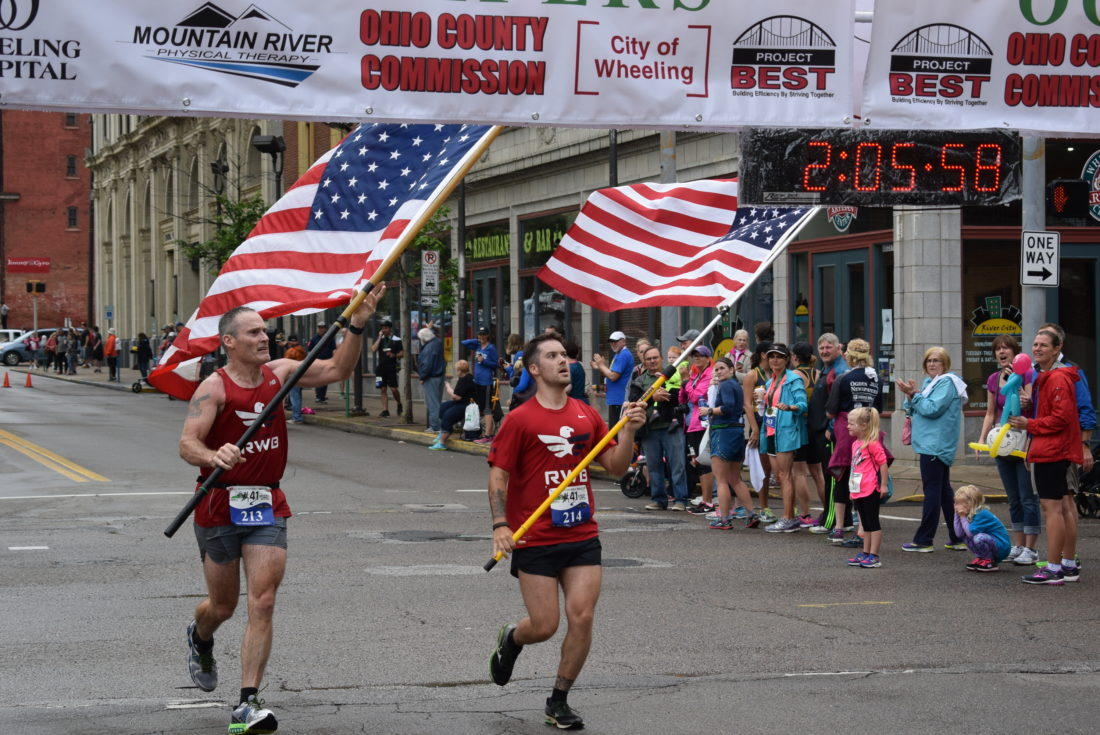 Photo by John McCabe Bearing American flags they carried for the duration of the 13.1-mile race, Shadyside residents Joe Foster, left, and his son, Cory Foster, cross the finish line during Saturday's Ogden Newspapers Half Marathon Classic.