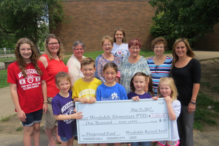 Photo Provided Retired staff members of Woodsdale Elementary School made a $1,000 donation to the school's playground project on Tuesday. Pictured in front from left are students Caroline Wack, Brennan Wack, Maddie Kirchner, Flannery Muscar and Gabby Kangisser. In the second row from left are Woodsdale student Shannon Wack, teacher Brandy LaFlam, former teacher Ceil Dumas, former teacher Debbie Kaiser, former principal Ruth Ann Scherich, former teacher Judy McNabb and former student Erika Weidner. Principal Ashlea Minch is shown in back.