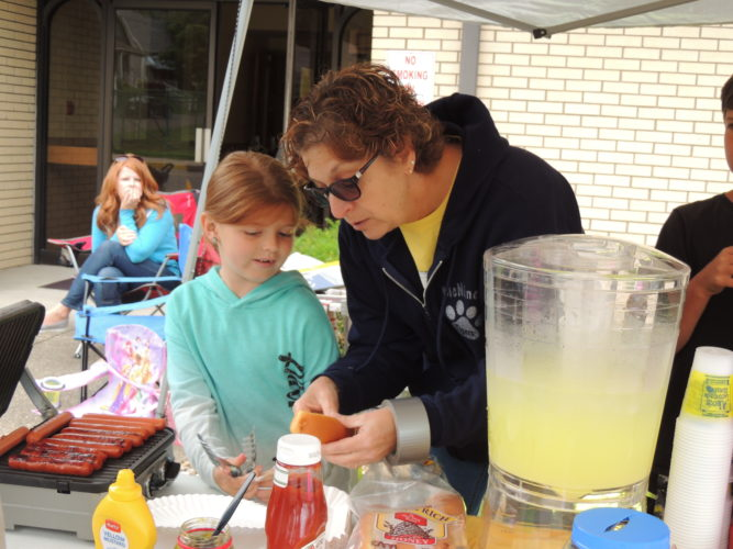 Brenda Crow, co-founder of the Marshall County                 Childhood  Cancer            Awareness Group, right, helps volunteer Brynna White prepare hot dogs at                 an Alex's Lemonade Stand          fundraiser in Moundsville.   Photo by                Drew Parker
