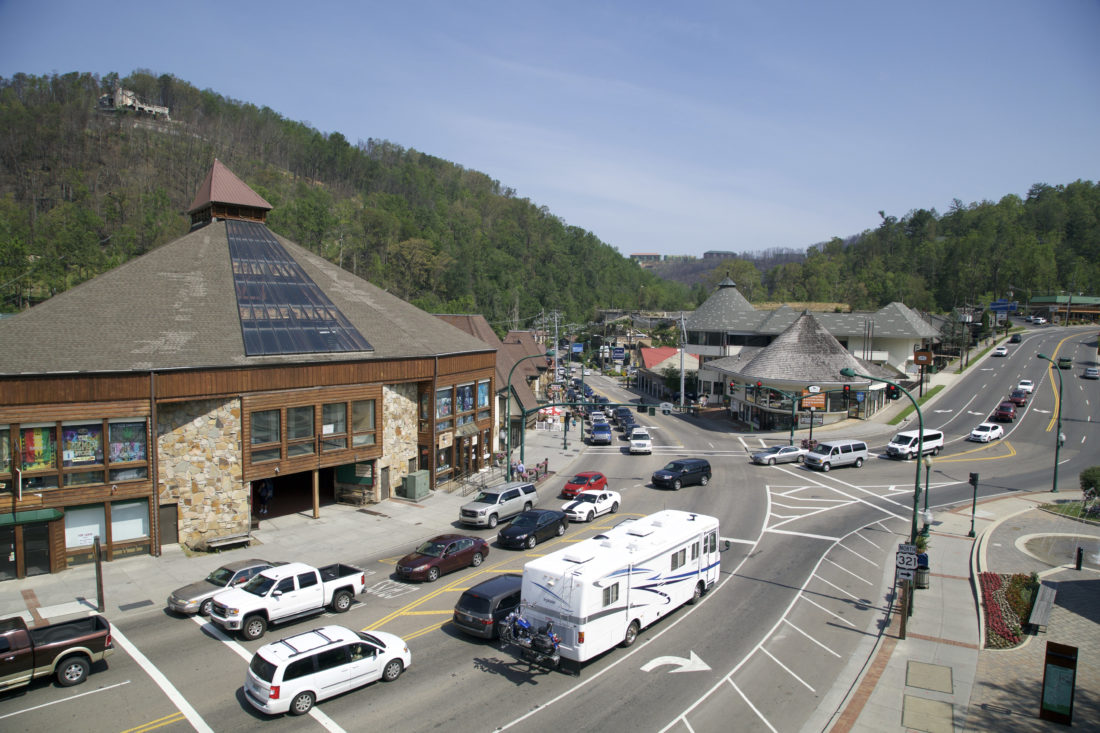 In this May 20, 2017 photo, a fire-damaged building overlooks cars driving through downtown Gatlinburg, Tennessee. A deadly wildfire in November of 2016 put a dent in the tourism industry, but signs of growth are returning. (AP Photo/Kristin Hall)