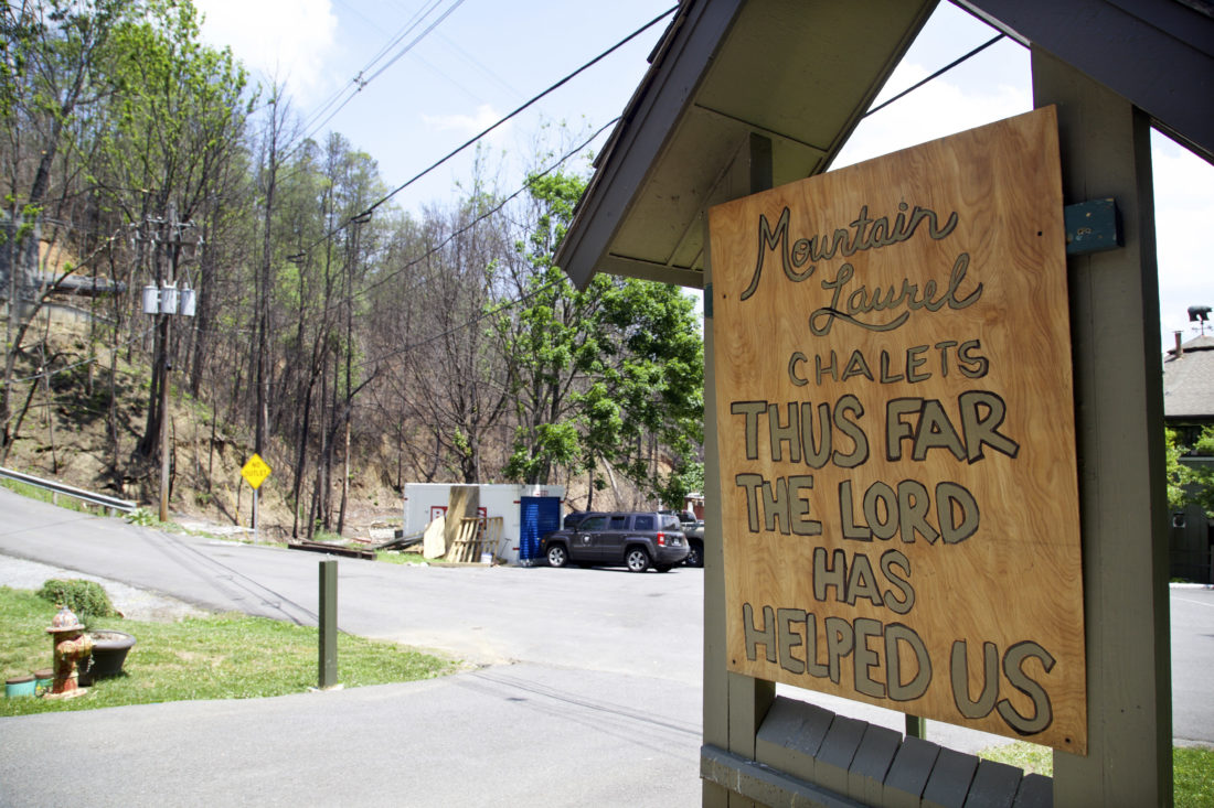 In this May 20, 2017 photo, a handmade sign stands in front of the fire-damaged Mountain Laurel Chalets. A deadly wildfire in November of 2016 put a dent in the tourism industry, but signs of growth are returning. (AP Photo/Kristin Hall)