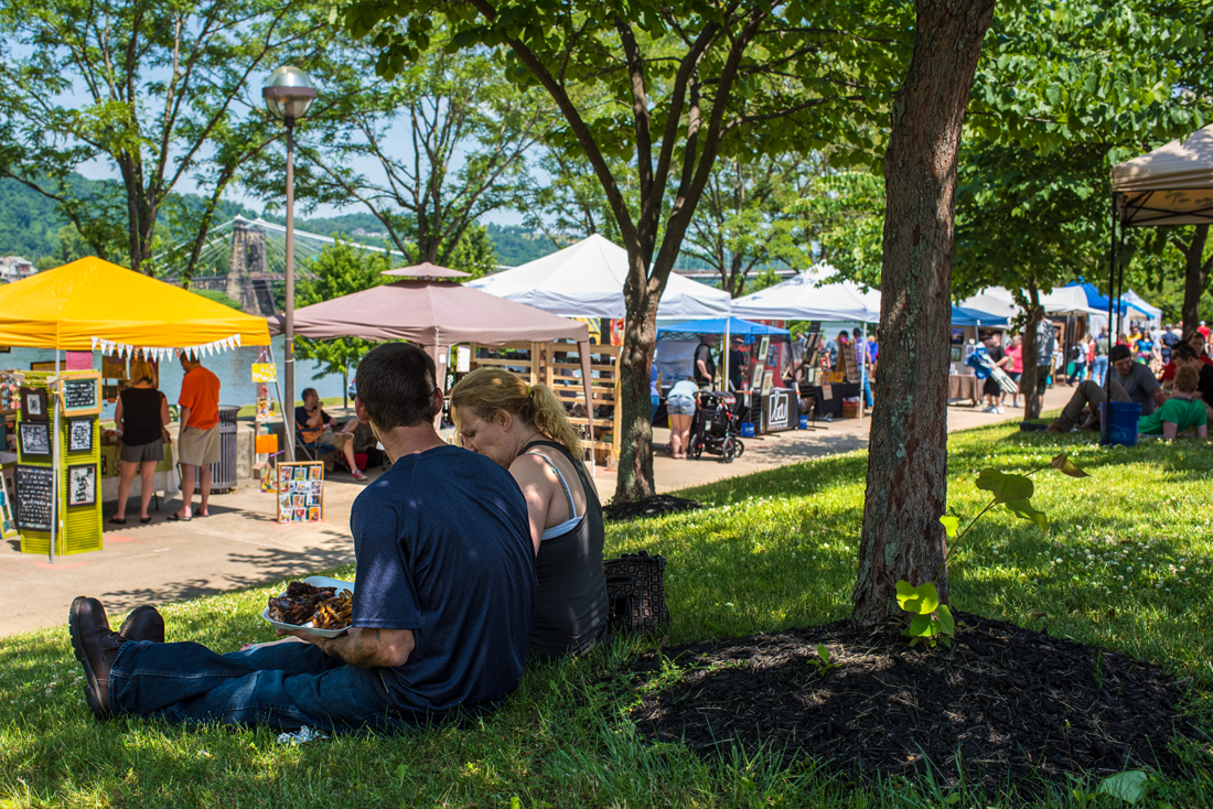 Festival-goers take a break under the trees at Wheeling Heritage Port during the 2016 Arts and Culture Fest. Below right, a spoken word artist performs.