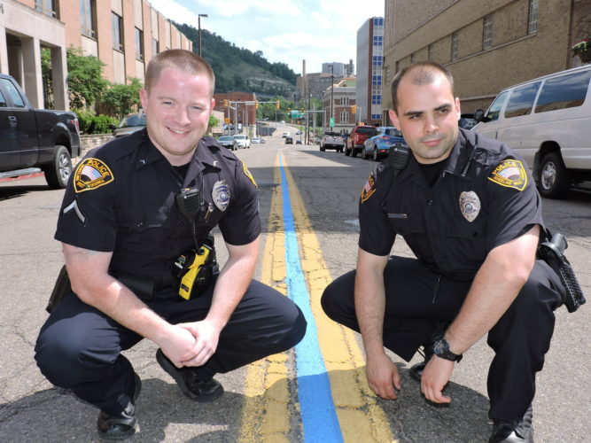 Photo by Casey Junkins To recognize the efforts of the city's police officers, including William Castilow, left, and Robert Agostino, Wheeling officials on Monday painted this blue line between the double yellow line in the middle of Chapline Street in front of the City-County Building.