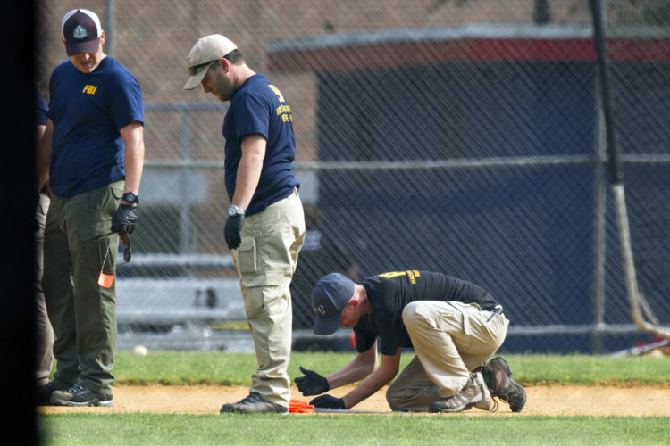 A FBI Evidence Response Team marks evidence on the ball field which is the scene of a multiple shooting in Alexandria, Va., Wednesday, June 14, 2017, after a rifle-wielding attacker opened fire on Republican lawmakers at a congressional baseball practice, wounding House GOP Whip Steve Scalise of Louisiana and several others as congressmen and aides dove for cover.  (AP Photo/Cliff Owen)