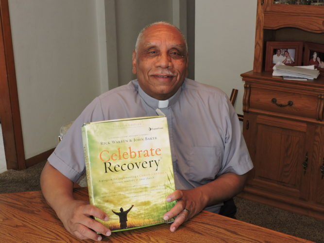 """Pastor Earnest Watkins displays  program materials for """"Celebrate  Recovery,"""" a plan he and Pastor Terry Endsley plan to offer the public starting next month.  Photo by Heather Ziegler"""