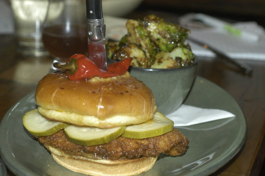 Shown is a spicy chicken sandwich with bread-and-butter zucchini and a side of carmelized Brussels sprouts at Rockmill Tavern in downtown Columbus.