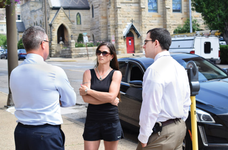 Photo by Scott McCloskey Angela Hawkins, the mother of 15-year-old Kyle Morgan, who was found dead beneath the Fort Henry Bridge last year, speaks with Wheeling police Sgt. Gregg McKenzie, left, and Detective Rob Safreed about the case Friday outside the City-County Building.