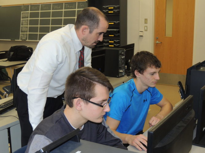 File Photo by Drew Parker John Marshall High School teacher Gavin Hartle, standing, assists students Harry Galloway, left, and Ryan Campbell with a computer-based project.