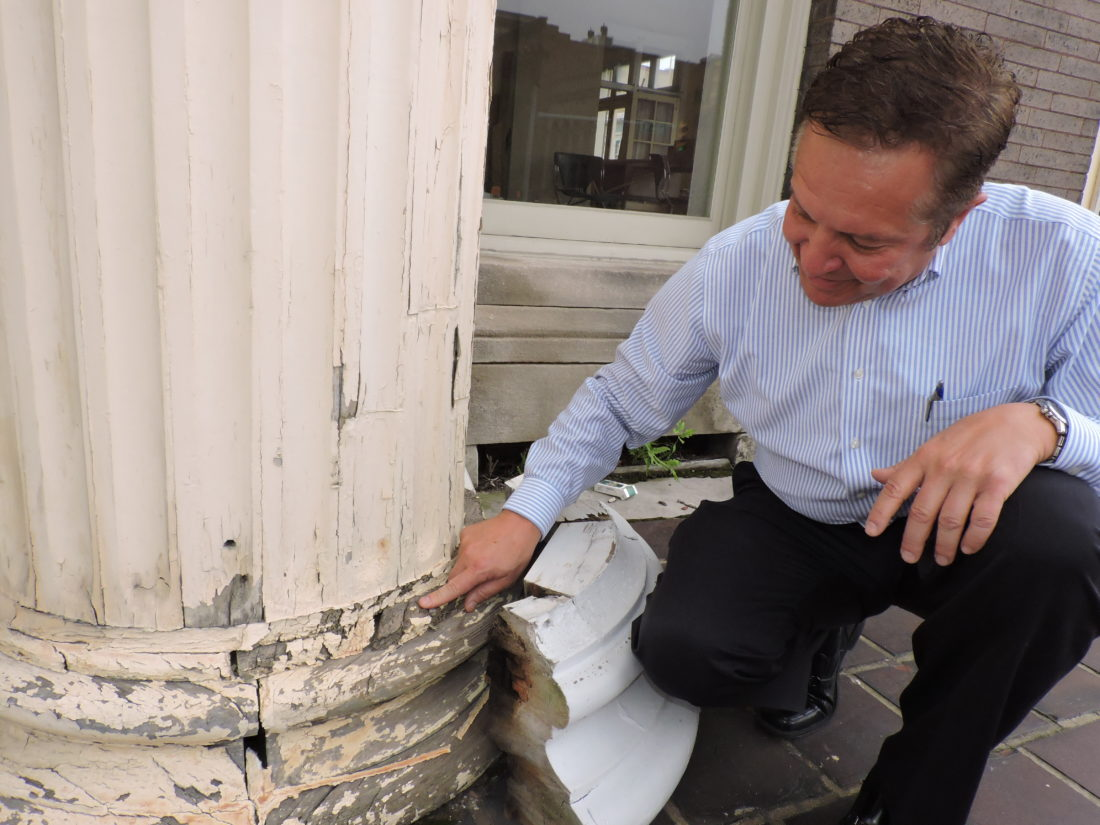 Photo by Casey Junkins Ernest Dellatorre, president of McKinley and Associates, which owns the Fort Henry Club building, shows one of the front porch columns the firm plans to repair.