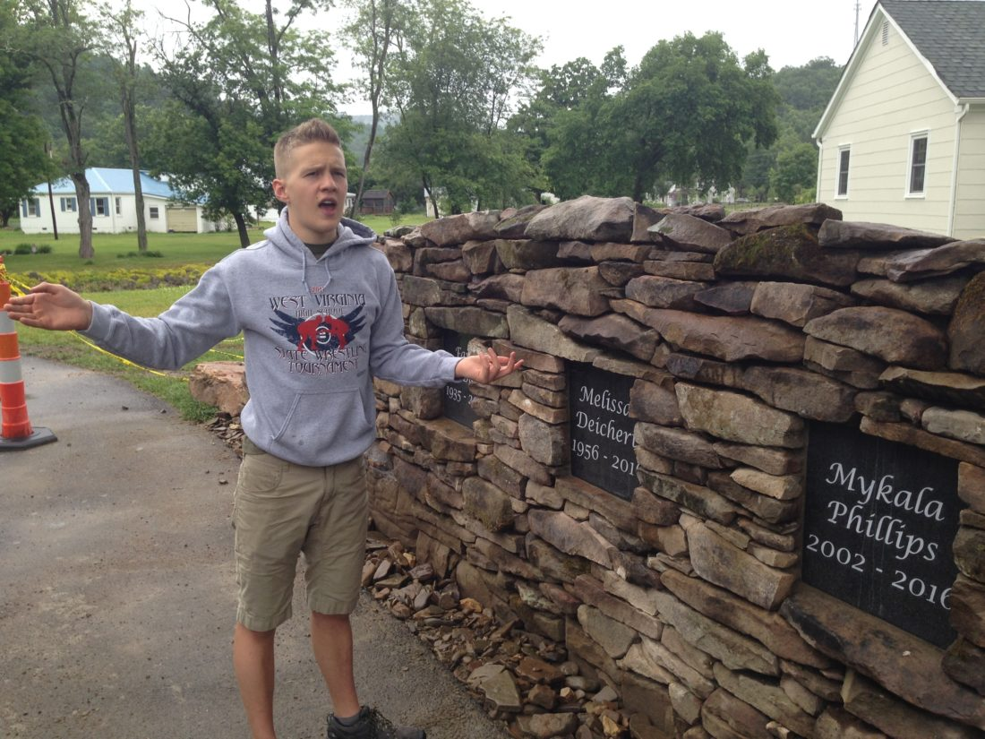 Teenager Cameron Zobrist stands next to a memorial wall honoring eight local flood victims Monday, June 5, 2017, in White Sulphur Springs, W.V. Zobrist came up with the idea for the wall for an Eagle Scout project. It was built through donated material, money and labor. A dedication ceremony for the memorial is set for June 23, 2017. Twenty-three people were killed in the floods statewide in June 2016. (AP Photo/John Raby)