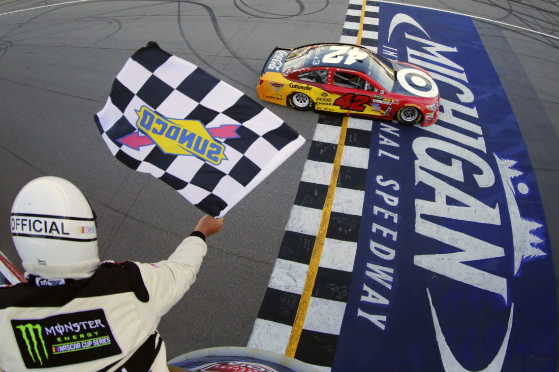 Kyle Larson takes the checkered flag to win the NASCAR Cup Series FireKeepers Casino 400 auto race at Michigan International Speedway, Sunday, June 18, 2017, in Brooklyn, Mich. (Chris Trotman/NASCAR via AP, Pool)