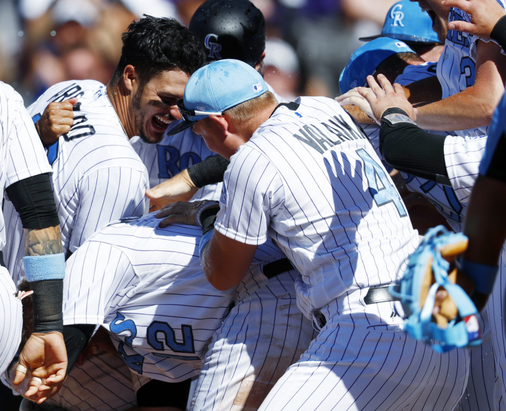 Colorado Rockies' Nolan Arenado, back, celebrates his three-run, walkoff home run with teammates Mark Reynolds, center, and Pat Valaika in the ninth inning of a baseball game against the San Francisco Giants Sunday, June 18, 2017, in Denver. The Rockies won 7-5. (AP Photo/David Zalubowski)`