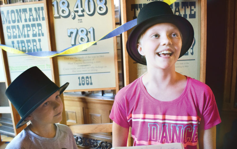 Photo by Scott McCloskey  Taylin Holt, 9, of Wheeling, foreground, and her brother, Blaise Holt, 7, wear top hats while enjoying West Virginia Day activities Tuesday at West Virginia Independence Hall in downtown Wheeling.