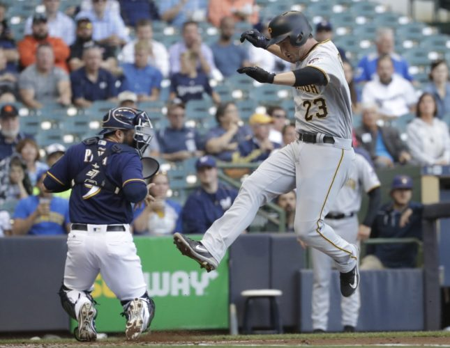 Pittsburgh Pirates' David Freese scores as Milwaukee Brewers catcher Manny Pina takes a late throw during the first inning of a baseball game Tuesday, June 20, 2017, in Milwaukee. (AP Photo/Morry Gash)