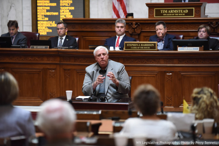 Photo by Perry Bennett, W.Va. Legislature West Virginia Gov. Jim Justice gestures during a May 17 address to House of Delegates members. On Wednesday, Justice announced he will allow the state budget to become law without his signature.