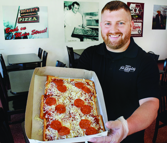 "Photo by Scott McCloskey Operations Manager Josh Beatty displays a box of the famous ""DiCarlos Pizza"" in the lobby of the downtown Wheeling shop."