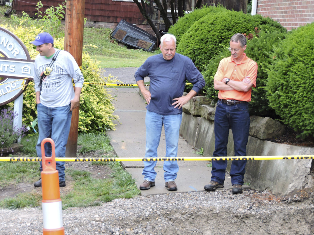 Photos by Dylan McKenzie  Martins Ferry Mayor Robert Krajnyak, center, stands with Assistant Fire Chief Jack Regis, left, and engineer Jeff Vaughn as they examine a sinkhole that opened Friday near the Jaycee Manor Apartments.