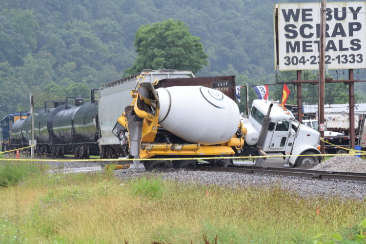 Photos by Scott McCloskey Emergency crews respond to a collision Friday morning between a cement truck and a train on an access road off W.Va. 2 in McMechen.