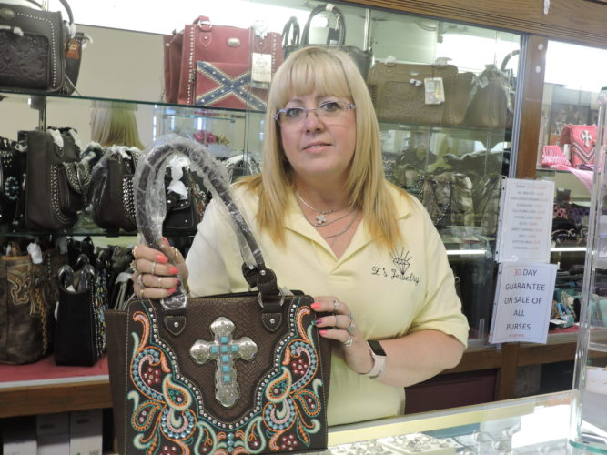 Stacey Long, manager of Z's Jewelry in Martins Ferry, shows off one of the many concealed     carry purses available for purchase at the shop. She said the store offers nearly 50  styles of          bags that are appropriate for carrying a        concealed weapon.  Photo by            Robert A. DeFrank