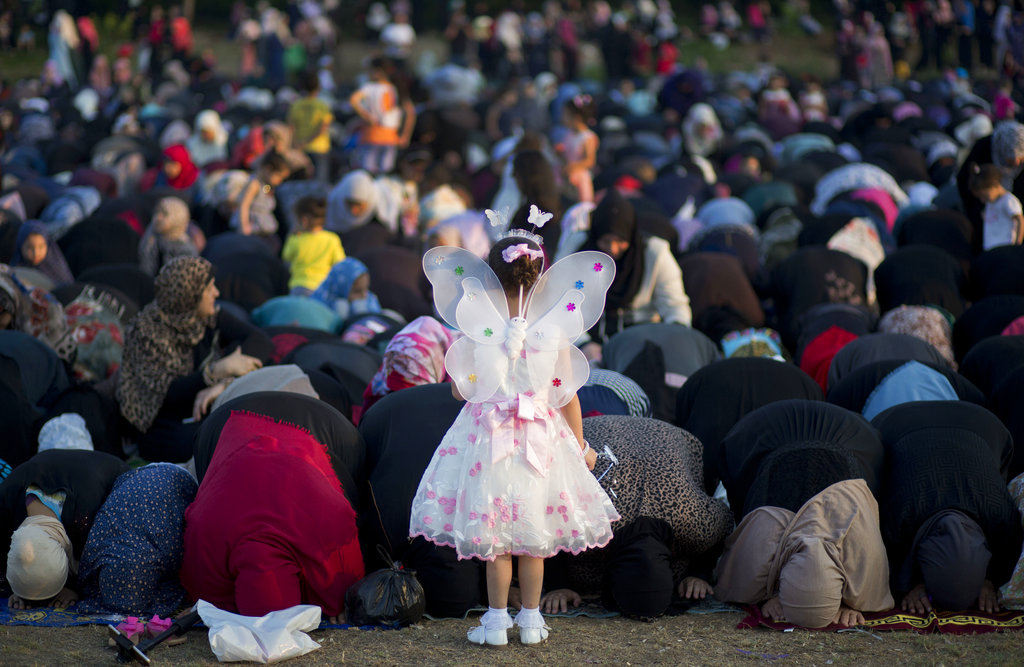 A Palestinian girl wears as a butterfly stand in front of women preforming at Eid al-Fitr prayers marking the end of the holy fasting month of Ramadan in Gaza City, Sunday, June 25, 2017. (AP Photo/ Khalil Hamra)