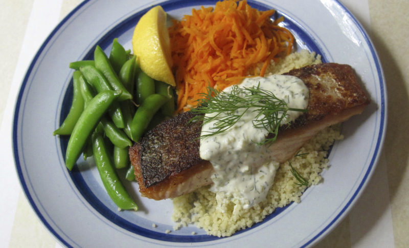 This May 30, 2017 photo shows salmon with crispy skin and pepperoncini lemon sauce in New York. This dish is from a recipe by Sara Moulton. (Sara Moulton via AP)