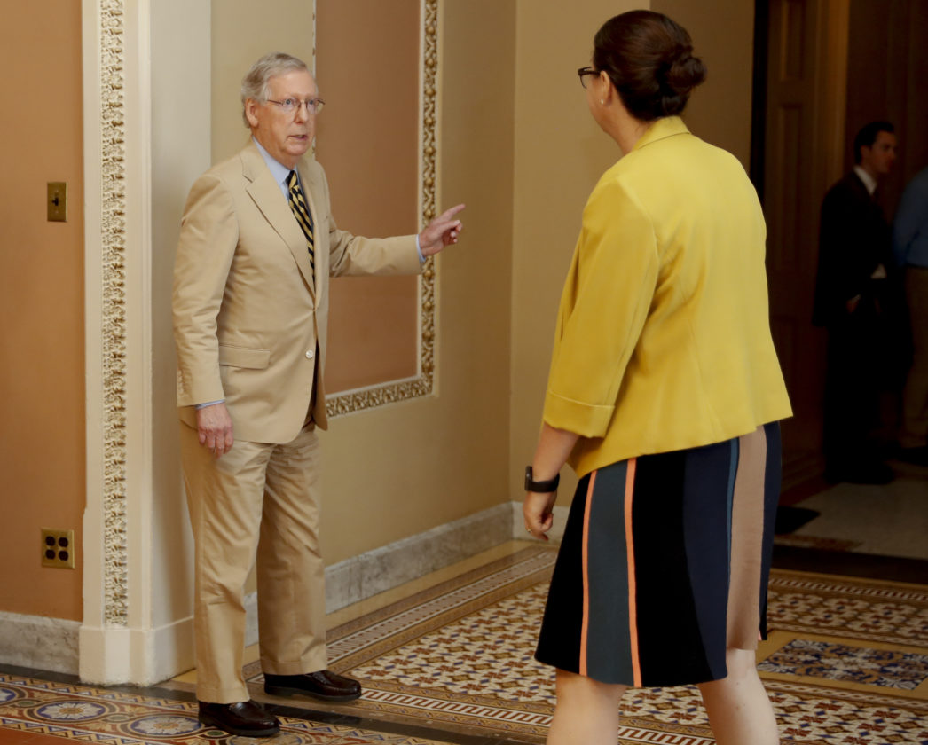Senate Majority Leader Mitch Mc Connell of Ky. talks with Secretary for the Majority Laura Dove as he walks to his office on Capitol Hill in Washington Monday