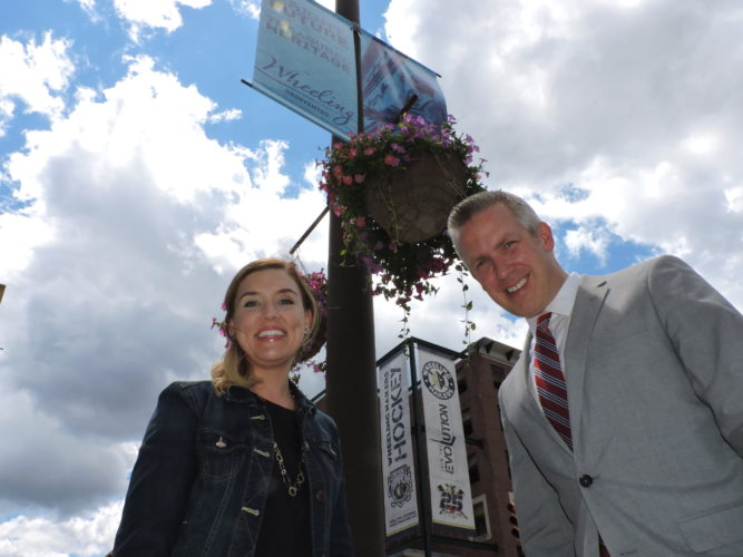 Photos by Casey Junkins Wheeling Marketing and Community Relations Specialist Allison Skibo joins Mayor Glenn Elliott at the corner of 14th and Main streets, as one of the city's new downtown banners hangs from the pole above them.