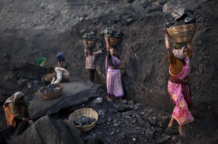 FILE - In this Friday, Jan. 7, 2011, file photo, people carry baskets of coal scavenged illegally at an open-cast mine in the village of Bokapahari in the eastern Indian state of Jharkhand where a community of coal scavengers live and work. The world's biggest coal users - China, the United States and India - have boosted coal mining in 2017, in an abrupt departure from last year's record global decline for the heavily polluting fuel and a setback to efforts to rein in climate change emissions. (AP Photo/Kevin Frayer, File)