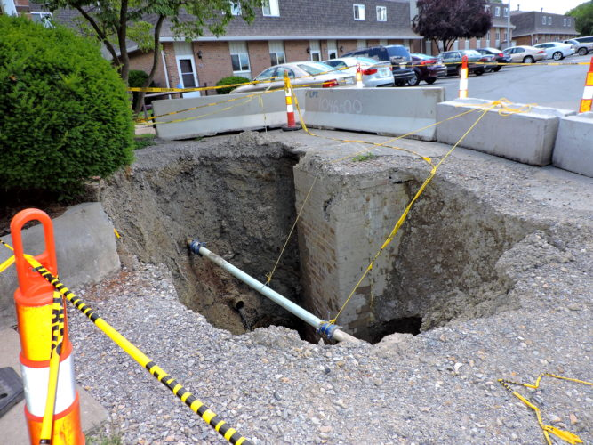 Photo by Shelley Hanson A sinkhole gapes in front of the Jaycee Manor Apartments in Martins Ferry.