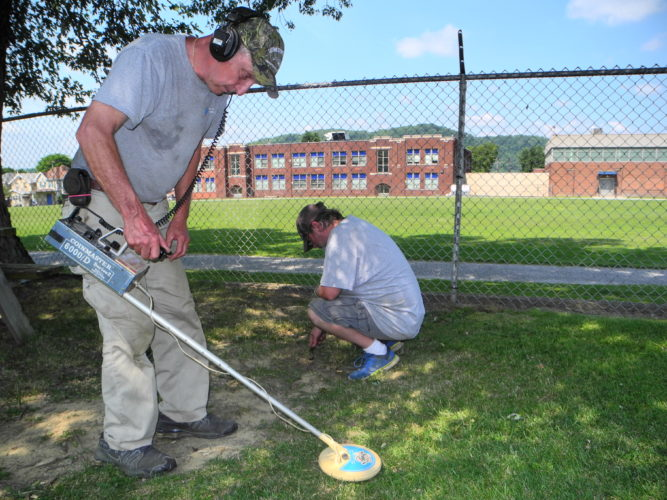Photo by Warren Scott Brian DaRe, an archaeologist working with Franciscan University of Steubenville, uses a metal detector over a possible site of a time capsule buried in Follansbee Park, while student Kurt Halligan digs.