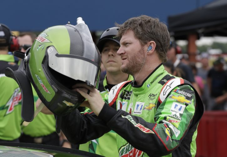 Dale Earnhardt Jr., reaches for his helmet before qualifying, Friday, June 16, 2017, for the NASCAR Sprint Cup series auto race in Brooklyn, Mich. (AP Photo/Carlos Osorio)