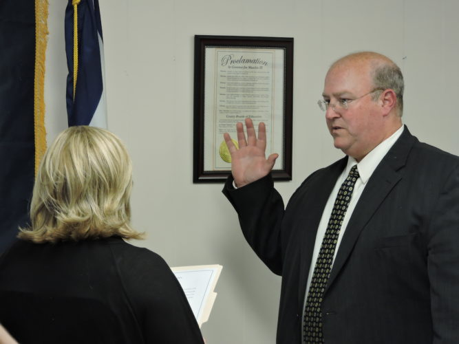 Photo by Alan Olson Incoming Marshall County Schools Superintendent Jeffrey Crook is sworn in by Jamie Crook during the board's Tuesday meeting.