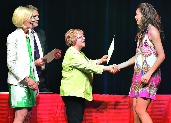 Photo by John McCabe Wheeling Park High School incoming senior Morgan Glass, right, is handed her Stifel award by Stifel Prize trustee Diane Crowl, center, as fellow trustee Joan Stamp, left and Ohio County Schools Federal Programs Coordinator Walter Saunders look on. The Stifel trustees handed out more than $134,000 Tuesday to about 200 Ohio County students in grades 5-12. The awards are based on a student's academic excellence.