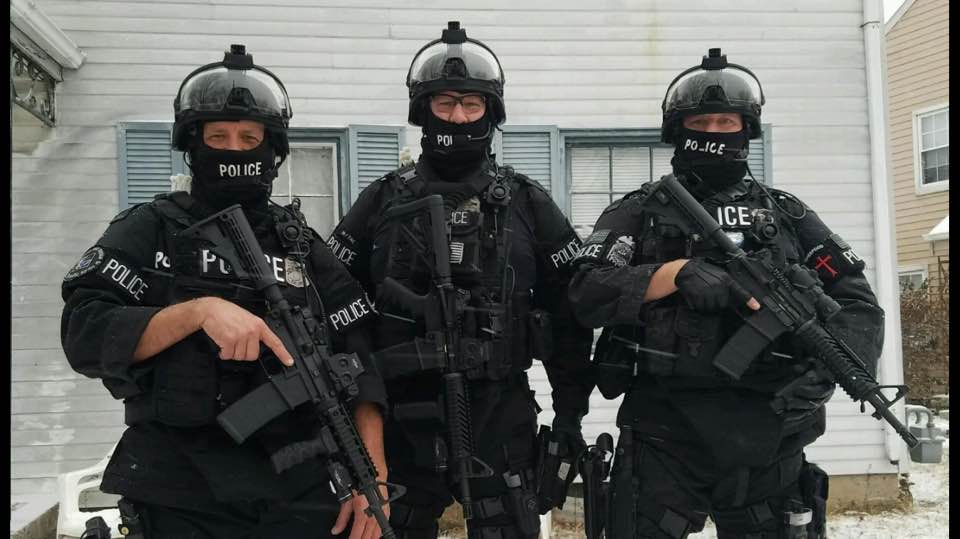 Photo Provided Martins Ferry native Patrick Shrodes, center, stands dressed in his SWAT gear with his fellow officers Joe Landis, left, and Todd Kaufman. Shrodes continues to recover after being shot by a suspect on March 15 in Columbus.