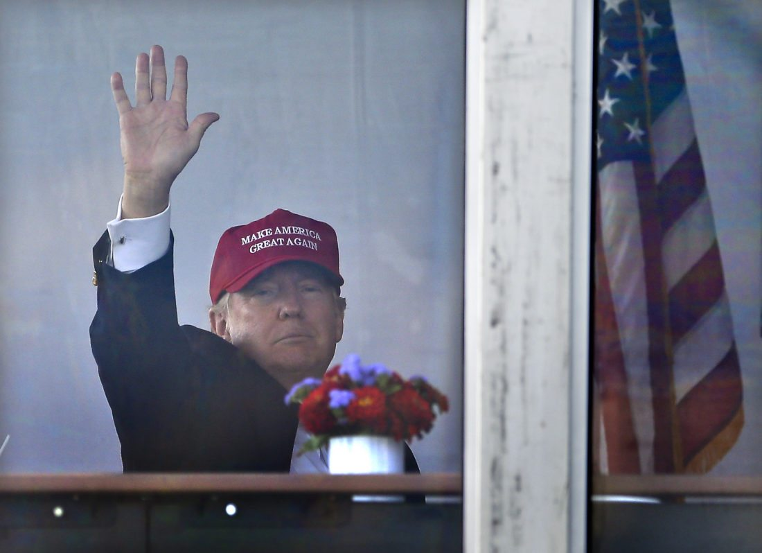 President Donald Trump waves to spectators as he watches the third round of the U.S. Women's Open Golf tournament from his observation booth, Saturday, July 15, 2017, in Bedminster, N.J. (AP Photo/Seth Wenig)
