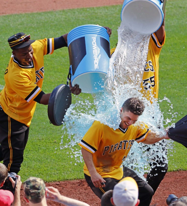 Pittsburgh Pirates' Adam Frazier, bottom, is doused by Gregory Polanco, left, and Josh Bell, rear, after driving in the game winning run with a walk-off single off St. Louis Cardinals relief pitcher Brett Cecil in the ninth inning of a of a baseball game in Pittsburgh, Sunday, July 16, 2017. The Pirates won 4-3.(AP Photo/Gene J. Puskar)