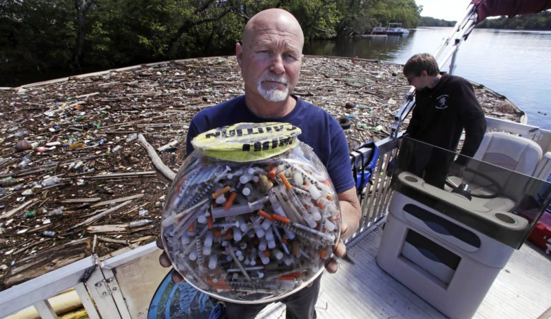 "In this Wednesday June 7, 2017 photo, activist Rocky Morrison, of the ""Clean River Project"", holds up a fish bowl filled with hypodermic needles, that were recovered during 2016, on the Merrimack River next to their facility in Methuen, Mass. Morrison leads a cleanup effort along the Merrimack River, which winds through the old milling city of Lowell, and has recovered hundreds of needles in abandoned homeless camps that dot the banks, as well as in piles of debris that collect in floating booms he recently started setting. (AP Photo/Charles Krupa)"