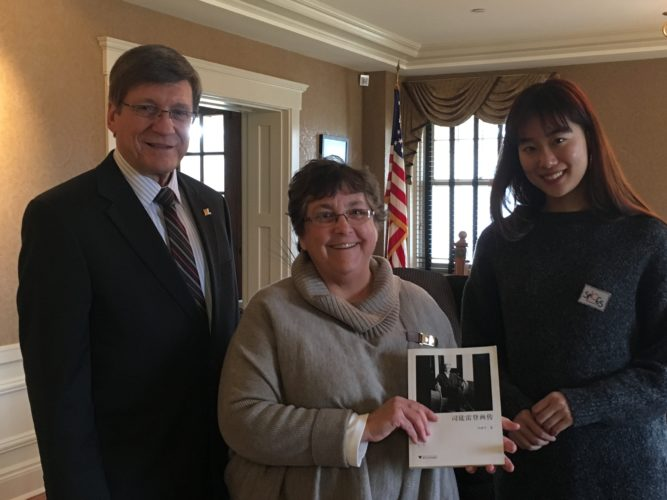 West Liberty University President Stephen Greiner and Elbin Library  Director Cheryl  Harshman accept the gift of a biographical book on Ambassador John Leighton Stuart from the author's daughter and WLU student, Yijing Shen.    Photo Provided