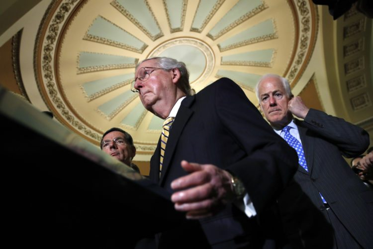 Senate Majority Leader Mitch McConnell of Ky., center, with Senate Majority Whip Sen. John Cornyn, R-Texas, right, and Sen. John Barrasso, R-Wyo., left, talks to reporters on Capitol Hill in Washington, Tuesday, July 25, 2017, after Vice President Mike Pence broke a 50-50 tie to start debating Republican legislation to tear down much of the Obama health care law. (AP Photo/Jacquelyn Martin)