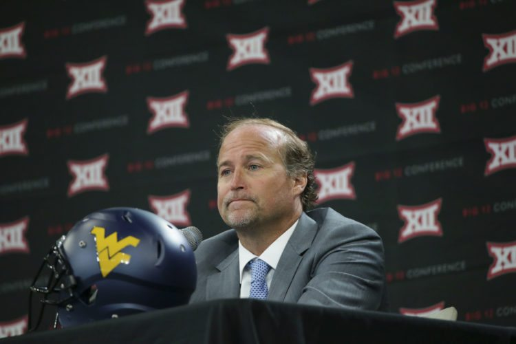 West Virginia head football coach Dana Holgorsen pages while speaking to reporters during the Big 12 NCAA college football media day in Frisco, Texas, Tuesday, July 18, 2017. (AP Photo/LM Otero)