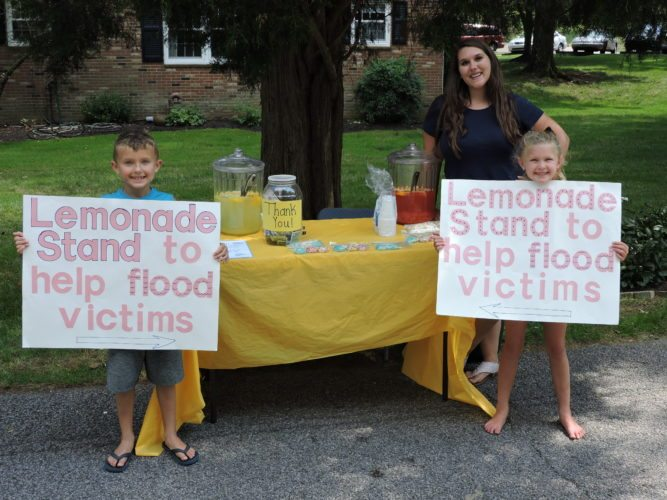 Photo by Alec Berry Seven-year-old twins Dominic and Luchia Fato, operate a lemonade stand near Wheeling Park on Thursday to benefit flood victims in McMechen as their babysitter, Emily Armstrong, supervises.