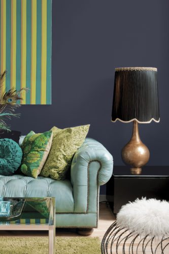 The PPG Paints hue Black Flame is shown on the wall of a living room. It was named 2018 Color of the Year by PPG Paints.