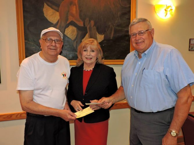Photo by Shelley Hanson Bellaire Sons of Italy members Phil Pata, left, and Larry Seibieda present a check for $1,000 to Helen Paes, community development coordinator with the Alzheimer's Association, for Alzheimer's disease research.