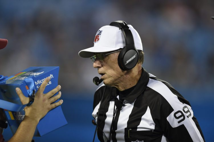 In this Wednesday, Aug. 9, 2017 photo, referee Tony Corrente (99) looks at the instant replay on a Microsoft Surface tablet during the second half of an NFL preseason football game between the Carolina Panthers and the Houston Texans in Charlotte, N.C. (AP Photo/Mike McCarn)