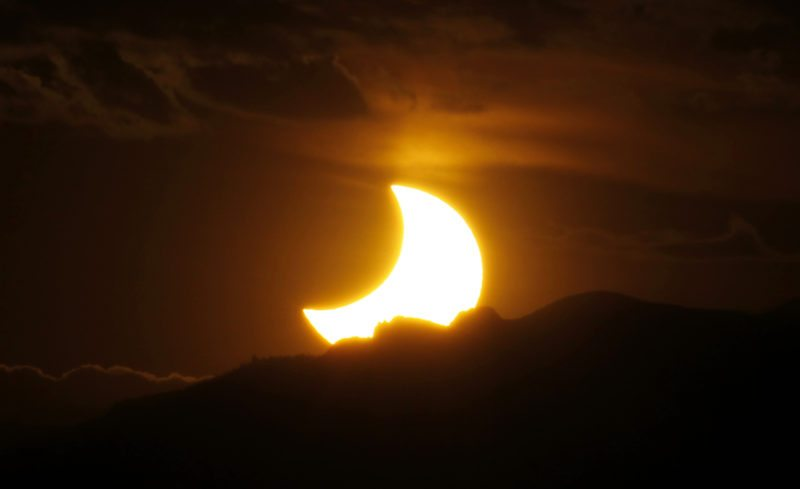 FILE - In this May 20, 2012, file photo, the annular solar eclipse is seen as the sun sets behind the Rocky Mountains from downtown Denver. Destinations are hosting festivals, hotels are selling out and travelers are planning trips for the total solar eclipse that will be visible coast to coast on Aug. 21. A narrow path of the United States 60 to 70 miles wide from Oregon to South Carolina will experience total darkness, also known as totality. (AP Photo/David Zalubowski, File)
